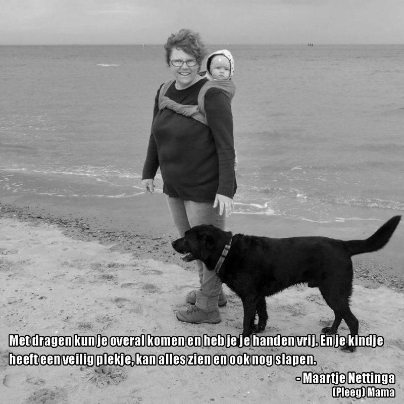 pleegmama op strand met hond en peuter op de rug met de tekst: Met dragen kun je overal komen, heb je je handen vrij En je kindje heeft een veilig plekje, kan alles zien en heerlijk slapen