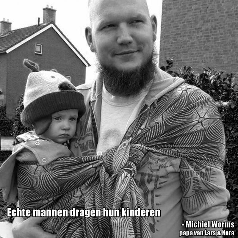 Papa met een dreumes op de heup in een draagdoek afgeknopt met een schuifknoop, met de tekst: Echte papa's dragen hun kinderen